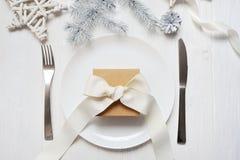 Πίνακας Χριστουγέννων που θέτει με ένα εκλεκτής ποιότητας δώρο στον άσπρο ξύλινο πίνακα Πρότυπο καρτών Χριστουγέννων με το διάστη Στοκ φωτογραφίες με δικαίωμα ελεύθερης χρήσης