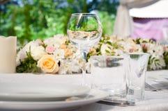 Πίνακες γαμήλιου συμποσίου που προετοιμάζονται για έναν γάμο έξω μια θερινή ημέρα Στοκ Εικόνες