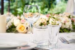 Πίνακες γαμήλιου συμποσίου που προετοιμάζονται για έναν γάμο έξω μια θερινή ημέρα Στοκ Φωτογραφίες