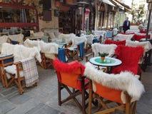 Πίνακες και καρέκλες καφετεριών οδών με το θερμό ύφασμα στην οδό Ιωάννινα Kalari Στοκ φωτογραφία με δικαίωμα ελεύθερης χρήσης