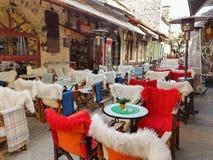 Πίνακες και καρέκλες καφετεριών οδών με το θερμό ύφασμα στην πόλη των Ιωαννίνων οδών Kalari Στοκ Φωτογραφία
