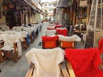 Πίνακες και καρέκλες καφετεριών οδών με το θερμό ύφασμα στην πόλη των Ιωαννίνων οδών Kalari Στοκ φωτογραφία με δικαίωμα ελεύθερης χρήσης