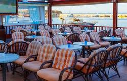 Πίνακες και καρέκλες σε έναν φραγμό προκυμαιών με τις απόψεις πέρα από το λιμάνι, Χερσόνησος, Κρήτη, Ελλάδα, Ευρώπη Στοκ Εικόνες