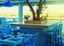 Πίνακες και καρέκλες σε έναν φραγμό προκυμαιών με τις απόψεις πέρα από το λιμάνι, Χερσόνησος, Κρήτη, Ελλάδα, Ευρώπη Στοκ εικόνα με δικαίωμα ελεύθερης χρήσης