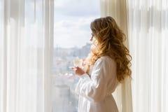 πίνοντας κορίτσι καφέ ομο&rh Όμορφες κουρτίνες ανοίγματος γυναικών, να φανεί έξω το παράθυρο και απόλαυση του καφέ πρωινού της Στοκ Φωτογραφία