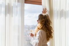 πίνοντας κορίτσι καφέ ομο&rh Όμορφες κουρτίνες ανοίγματος γυναικών, να φανεί έξω το παράθυρο και απόλαυση του καφέ πρωινού της Στοκ Εικόνες