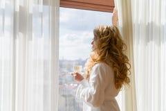 πίνοντας κορίτσι καφέ ομο&rh Όμορφες κουρτίνες ανοίγματος γυναικών, να φανεί έξω το παράθυρο και απόλαυση του καφέ πρωινού της Στοκ Εικόνα