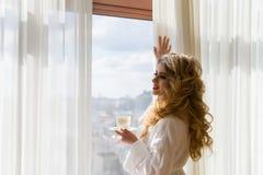 πίνοντας κορίτσι καφέ ομο&rh Όμορφες κουρτίνες ανοίγματος γυναικών, να φανεί έξω το παράθυρο και απόλαυση του καφέ πρωινού της Στοκ εικόνες με δικαίωμα ελεύθερης χρήσης