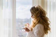 πίνοντας κορίτσι καφέ ομο&rh Όμορφες κουρτίνες ανοίγματος γυναικών, να φανεί έξω το παράθυρο και απόλαυση του καφέ πρωινού της Στοκ Φωτογραφίες