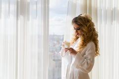 πίνοντας κορίτσι καφέ ομο&rh Όμορφες κουρτίνες ανοίγματος γυναικών, να φανεί έξω το παράθυρο και απόλαυση του καφέ πρωινού της Στοκ φωτογραφία με δικαίωμα ελεύθερης χρήσης