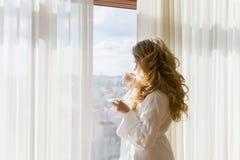 πίνοντας κορίτσι καφέ ομο&rh Όμορφες κουρτίνες ανοίγματος γυναικών, να φανεί έξω το παράθυρο και απόλαυση του καφέ πρωινού της Στοκ φωτογραφίες με δικαίωμα ελεύθερης χρήσης