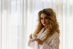 πίνοντας κορίτσι καφέ ομο&rh Όμορφες κουρτίνες ανοίγματος γυναικών, να φανεί έξω το παράθυρο και απόλαυση του καφέ πρωινού της Στοκ εικόνα με δικαίωμα ελεύθερης χρήσης