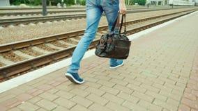 Πίσω άποψη: Ένα άτομο με μια τσάντα ταξιδιού πηγαίνει κατά μήκος του σιδηροδρόμου Μόνο τα πόδια είναι ορατά στο πλαίσιο steadicam απόθεμα βίντεο