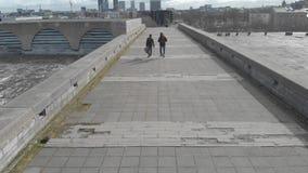 Πίσω άποψη δύο ανθρώπων με τις κιθάρες που περπατούν σε μια μεγάλη γκρίζα γέφυρα ενάντια στα μπλε νεφελώδη κτήρια ουρανού και πόλ φιλμ μικρού μήκους