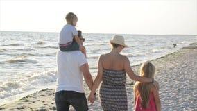 Πίσω άποψη δύο μικρών αδελφών και της ευτυχών μητέρας και του πατέρα που περπατούν μαζί γύρω από τα χέρια εκμετάλλευσης παραλιών  απόθεμα βίντεο