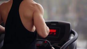 Πίσω άποψη ενός αθλητικού ισχυρού ατόμου που τρέχει treadmill Ισχυροί ώμοι, όπλα και πλάτη Επίλυση σε μια αθλητική λέσχη απόθεμα βίντεο