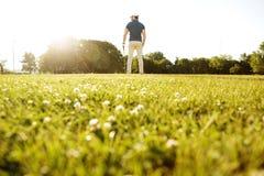 Πίσω άποψη ενός αρσενικού φορέα γκολφ στην πράσινη σειρά μαθημάτων με μια λέσχη Στοκ Εικόνες