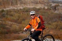πίσω άποψη ενός ατόμου με ένα ποδήλατο και του κόκκινου σακιδίου πλάτης ενάντια στο μπλε ουρανό ο ποδηλάτης οδηγά ένα ποδήλατο Στοκ εικόνες με δικαίωμα ελεύθερης χρήσης
