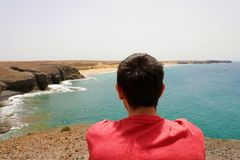 Πίσω άποψη ενός ατόμου συνεδρίασης που απολαμβάνει το τοπίο Lanzarote Playas de Papagayo, Κανάρια νησιά Στοκ φωτογραφία με δικαίωμα ελεύθερης χρήσης