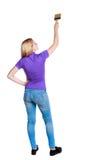 Πίσω άποψη ενός κοριτσιού που χρωματίζει τον κύλινδρο χρωμάτων Στοκ εικόνα με δικαίωμα ελεύθερης χρήσης