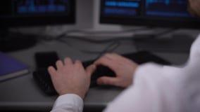 Πίσω άποψη ενός νέου επιχειρηματία με το smartwatch σε ετοιμότητα του που λειτουργεί στο γραφείο του στο γραφείο Εικόνα των χεριώ απόθεμα βίντεο