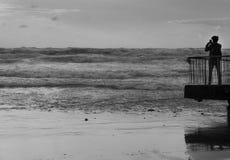 Πίσω άποψη ενός τουρίστα που παίρνει τη φωτογραφία της θύελλας θάλασσας με το smartphone στην μπροστινή θάλασσα Στοκ Εικόνες