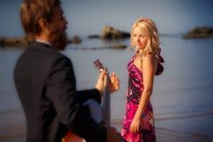 Πίσω-άποψη κιθαριστών και ξανθό κορίτσι ενάντια στη θάλασσα Στοκ Φωτογραφία