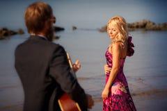 Πίσω-άποψη κιθαριστών και ξανθό κορίτσι ενάντια στη θάλασσα Στοκ Εικόνες
