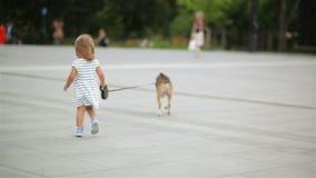 Πίσω άποψη λίγου χαριτωμένου κοριτσιού που περπατά με το σκυλί λαγωνικών της σε ολόκληρη την πόλη τετραγωνική και που κρατά τη Pe φιλμ μικρού μήκους