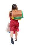 Πίσω άποψη μιας γυναίκας που πηδά με τις τσάντες αγορών Στοκ Εικόνες