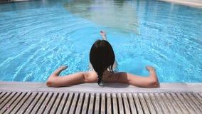 Πίσω άποψη μιας γυναίκας που χαλαρώνει στην πισίνα απόθεμα βίντεο