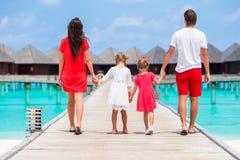 Πίσω άποψη μιας ευτυχούς οικογένειας στην τροπική παραλία Στοκ Φωτογραφία