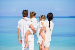 Πίσω άποψη μιας ευτυχούς οικογένειας στην τροπική παραλία Στοκ φωτογραφία με δικαίωμα ελεύθερης χρήσης