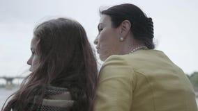 Πίσω άποψη μιας κομψής ώριμης συνεδρίασης γυναικών στο riverbank, που αγκαλιάζει με τη χαριτωμένη εγγονή της r απόθεμα βίντεο