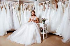 Πίσω άποψη μιας νέας γυναίκας στο γαμήλιο φόρεμα που εξετάζει τις νυφικές εσθήτες στοκ φωτογραφίες