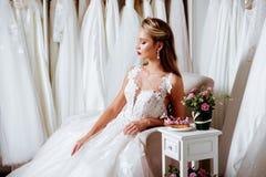 Πίσω άποψη μιας νέας γυναίκας στο γαμήλιο φόρεμα που εξετάζει τις νυφικές εσθήτες στοκ εικόνες