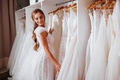 Πίσω άποψη μιας νέας γυναίκας στο γαμήλιο φόρεμα που εξετάζει τις νυφικές εσθήτες στοκ φωτογραφίες με δικαίωμα ελεύθερης χρήσης