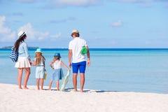 Πίσω άποψη μιας νέας οικογένειας στην τροπική παραλία Στοκ Εικόνα