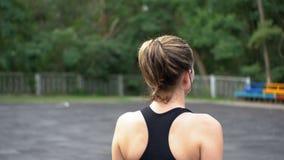 Πίσω άποψη σχετικά με τη νέα γυναίκα αθλητών στην αθλητική εξάρτηση που περπατά κατά μήκος του αθλητισμού Feld στο πάρκο απόθεμα βίντεο