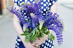 Πίσω άποψη σχετικά με το κορίτσι που κρατά μια δέσμη των όμορφων λουλουδιών lupine Π Στοκ Εικόνες