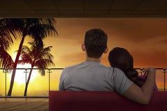 Πίσω άποψη της ασιατικής χαλάρωσης ζευγών στον καναπέ και της απόλαυσης του ηλιοβασιλέματος Στοκ Φωτογραφίες