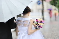 Πίσω άποψη της γαμήλιας ανθοδέσμης εκμετάλλευσης νυφών Στοκ Φωτογραφία