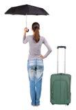 Πίσω άποψη της γυναίκας με την ομπρέλα που ταξιδεύει με τα suitcas Στοκ Εικόνες