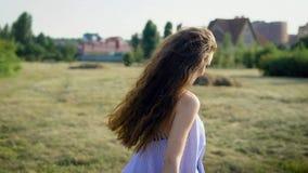Πίσω άποψη της γυναίκας με τη μακρυμάλλη τοποθέτηση στο υπόβαθρο της επαρχίας που κοιτάζει μακριά στον ήλιο φιλμ μικρού μήκους