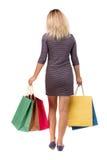Πίσω άποψη της γυναίκας με τις τσάντες αγορών όμορφο κορίτσι brunette στην κίνηση πρόσωπο πίσω πλευρών Στοκ Εικόνες
