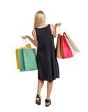 Πίσω άποψη της γυναίκας με τις τσάντες αγορών όμορφο κορίτσι brunette στην κίνηση πρόσωπο πίσω πλευρών Στοκ εικόνα με δικαίωμα ελεύθερης χρήσης