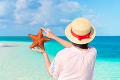 Πίσω άποψη της γυναίκας με τον αστερία στα χέρια στην άσπρη παραλία στην επιφύλαξη φύσης στοκ εικόνες