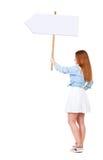 Πίσω άποψη της γυναίκας που παρουσιάζει πίνακα σημαδιών Στοκ Φωτογραφίες