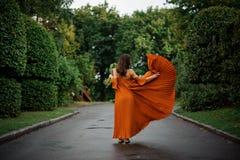 Πίσω άποψη της ελκυστικής γυναίκας στο μακρύ πορτοκαλί φόρεμα με τα λουλούδια Στοκ εικόνες με δικαίωμα ελεύθερης χρήσης