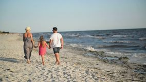 Πίσω άποψη της ευτυχούς οικογένειας με λίγη κόρη που περπατά σε ετοιμότητα εκμετάλλευσης παραλιών κατά τη διάρκεια των θερινών δι απόθεμα βίντεο